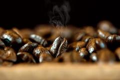 与热烟的咖啡豆 做热的饮料的barista的新鲜的咖啡因 库存图片