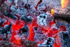 与热的火焰的燃烧的和发光的木炭在背景中 图库摄影