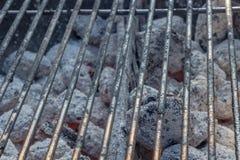 与热的煤炭的烤肉格床制煤砖在它下 免版税库存照片