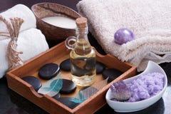 与热的石头的芳香油在一个木箱的按摩的在毛巾、紫色盐和牛奶旁边在椰子 图库摄影