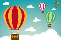 与热空气气球的假日背景在与云彩的减速火箭的色的蓝天 免版税库存照片