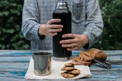 与热水瓶、曲奇饼、面包和金属杯子的室外午餐场面 免版税库存照片