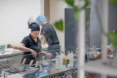 与烹调意大利食物的工作的厨师和厨师的开放厨房服务在现代餐馆 免版税库存照片