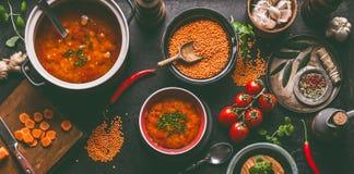 与烹调成份的红色小扁豆汤在黑暗的土气厨房用桌背景,顶视图 健康素食主义者食物概念 素食主义者 免版税库存图片