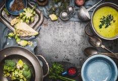 与烹调成份、厨房工具、杓子、碗和匙子的绿色Romanesco和硬花甘蓝汤在黑暗的土气背景,上面 免版税库存图片