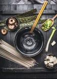 与烹调成份的大酱汤准备:乌龙面面条、豆腐、什塔克菇、nori和葱在黑暗的土气后面 库存图片