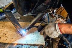 与焊接器的人焊接 库存照片