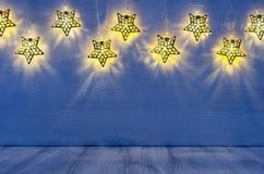 与焕发的圣诞节空白的内部点燃在靛蓝色木头背景的黄色星 免版税库存照片