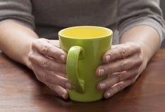 与焦点的严肃的反射在绿色咖啡杯在缓慢的早晨或一个舒适的断裂的 库存图片
