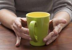 与焦点的反射在绿色咖啡杯在缓慢的早晨或舒适的断裂的 免版税库存照片