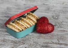 与焦糖奶油和核桃在葡萄酒金属箱子,明亮的木表面上的装饰红色心脏的曲奇饼 免版税库存图片