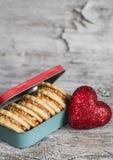 与焦糖奶油和核桃在葡萄酒金属箱子,明亮的木表面上的装饰红色心脏的曲奇饼 库存图片