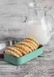 与焦糖奶油和核桃的一种油脂含量较高的酥饼在葡萄酒金属箱和一个投手牛奶 免版税库存图片