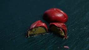 与焦糖装填的整个和切成两半的小红色巧克力糖 股票视频