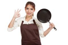 与煎锅的亚洲女孩厨师展示OK 库存图片