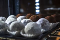 与照明的玻璃展示窗口在咖啡馆用白色球的糖果和巧克力 鲜美甜点 蛋糕 库存图片