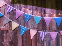 与照明设备串的各种各样的被仿造的三角旗子在木板条背景 免版税库存图片