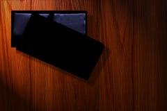 与照明设备的黑匣子包装的豪华在木背景 库存照片