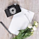 与照相机、玫瑰、笔记本、耳机和笔的平的位置样式 免版税图库摄影