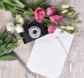 与照相机、玫瑰、笔记本、耳机和笔的平的位置样式 库存图片