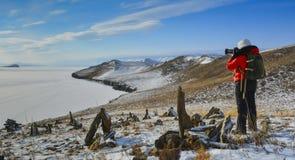 与照相机的女孩旅行 她射击惊人的风景在山顶部 免版税图库摄影