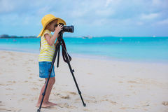 与照相机的小女孩射击在一个三脚架在她的暑假时 库存照片