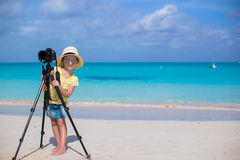 与照相机的小女孩射击在三脚架在期间 免版税库存照片