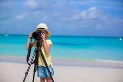 与照相机的小女孩射击在三脚架在期间 库存照片