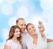 与照相机的愉快的家庭在家 库存照片