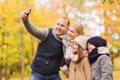 与照相机的愉快的家庭在秋天公园 免版税库存照片