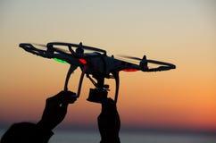 与照相机的飞行寄生虫在日落的天空 库存图片
