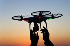 与照相机的飞行寄生虫在日落的天空 免版税库存照片