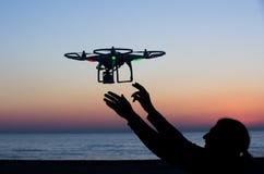与照相机的飞行寄生虫在日落的天空 免版税图库摄影