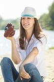 与照相机的年轻俏丽的妇女作为乐趣在海滩 免版税图库摄影