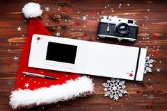 与照相机,红色帽子、笔记薄和照片框架的圣诞节背景 图库摄影