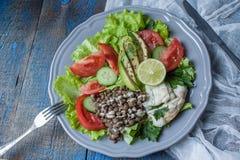 与煮沸的鳕鱼,扁豆, tahini,荷兰芹,蕃茄的健康蔬菜沙拉 免版税库存图片