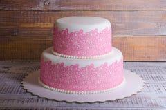与熊和兔宝宝的两层方旦糖婚礼鞋带蛋糕 库存图片