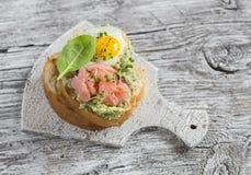 与熏制鲑鱼和煎鹌鹑蛋的被捣碎的鲕梨三明治 一顿可口早餐或快餐 免版税库存照片