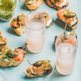与熏制鲑鱼和粉红色葡萄柚鸡尾酒,方形的庄稼的Crostini 库存图片