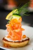 与熏制鲑鱼和酸性稀奶油的一道俄式薄煎饼开胃菜,被装饰 库存照片