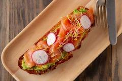与熏制鲑鱼的健康早餐和鲕梨敬酒 免版税图库摄影
