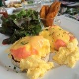 与熏制鲑鱼的鸡蛋本尼迪克特冠上用新鲜的草本和蛋黄奶油酸辣酱调味汁服务用蔬菜沙拉和炸薯条与迷离 库存图片