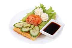 与熏制鲑鱼,莴苣叶子,黄瓜切片的比利时华夫饼干 免版税库存图片