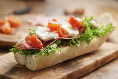 与熏火腿、无盐干酪和蕃茄的单片三明治在厨房用桌上 库存照片