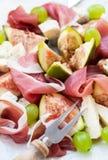 与熏火腿、无花果、乳酪和葡萄的开胃菜 库存照片