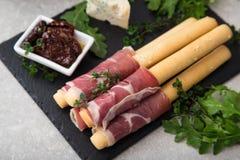 与熏火腿、火腿、青纹干酪和各式各样的tomat的开胃菜 图库摄影