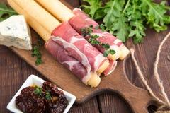 与熏火腿、火腿、青纹干酪和各式各样的tomat的开胃菜 免版税库存图片