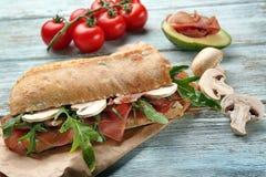 与熏火腿、芝麻菜和蘑菇的鲜美三明治在木桌上 库存图片