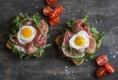 与熏火腿、芝麻菜和煎鹌鹑蛋的三明治在木背景,顶视图 鲜美早餐,快餐 库存照片