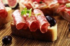 与熏火腿的三明治或蒜味咸腊肠或者crudo 开胃小菜食家b 图库摄影